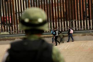 A National Guard soldier observes migrants after crossing illegally into El Paso, Texas, U.S. to turn themselves in to U.S. Border Patrol agents to ask for asylum, as seen from Ciudad Juarez, Mexico September 15, 2019. REUTERS/Jose Luis Gonzalez