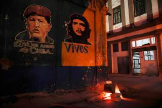 Images depicting Venezuela's late president Hugo Chavez (L), with words that read