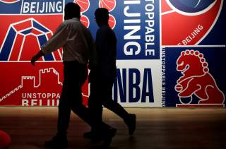 Men walk past a poster at an NBA exhibition in Beijing, China October 8, 2019. REUTERS/Jason Lee/File Photo