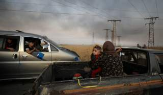 A woman with a baby sits at a back of a truck as they flee Ras al Ain town, Syria October 9, 2019. REUTERS/Rodi Said TPX IMAGES OF THE DAY