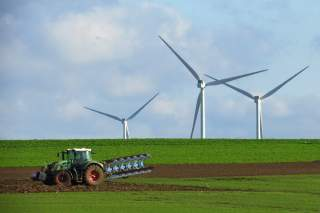 A French farmer drives a tractor as he ploughs a field in front of power-generating windmill turbines on a wind park in Havrincourt, France, November 10, 2019. Picture taken November 10, 2019. REUTERS/Pascal Rossignol