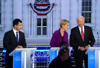 South Bend Mayor Pete Buttigieg looks on as Senator Elizabeth Warren and former Vice President Joe Biden talk during a break in the U.S. Democratic presidential candidates debate at the Tyler Perry Studios in Atlanta, Georgia, U.S. November 20, 2019.