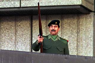 President Saddam Hussein fires a rifle in the air as he salutes Iraqi volunteers who have offered to fight with Paleastinians against Israel troops during a military parade in Baghdad on November 20, 2000. Almost two million men, women and teenagers, some