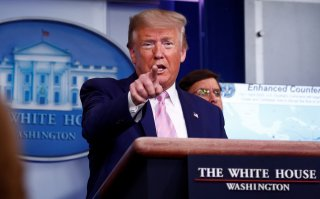 U.S. President Donald Trump speaks as U.S. Defense Secretary Mark?Esper listens during the coronavirus daily briefing at the White House in Washington, U.S., April 1, 2020. REUTERS/Tom Brenner
