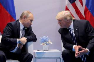 Russia's President Vladimir Putin talks to U.S. President Donald Trump during their bilateral meeting at the G20 summit in Hamburg, Germany, July 7, 2017. REUTERS/Carlos Barria//File Photo