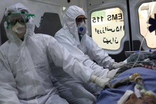 Emergency medical staff wearing protective suits, sit in an ambulance while transferring a patient with coronavirus disease (COVID-19) to Masih Daneshvari Hospital, in Tehran, Iran March 30, 2020. WANA (West Asia News Agency)/Ali Khara via REUTERS