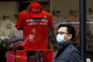 A man in a surgical mask walks by goods for sale emblazoned with U.S. President Donald Trump's 2016 campaign slogan