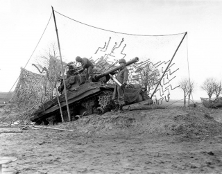 SC 197925. Btry C, 702nd Tank Destroyer Battalion, 2nd Armored Division, tank destroyer on dug-in ramp has plenty of elevation to hurl shells at long range enemy targets across the Roer River. (16 Dec 1944).