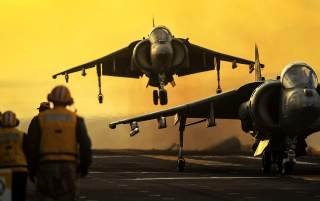 An AV-8B Harrier from Marine Attack Squadron (VMA) 214 performs a vertical take off from the flight deck of the amphibious assault ship USS Boxer (LHD 4).