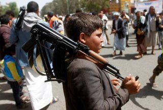 A boy carries a weapon as he and Houthi supporters are seen during a gathering in Sanaa, Yemen April 2, 2020. REUTERS/Mohamed al-Sayaghi
