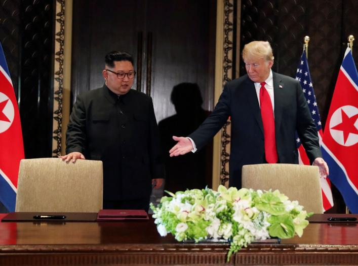 FILE PHOTO: U.S. President Donald Trump and North Korea's leader Kim Jong Un (L) arrive to sign a document to acknowledge the progress of the talks and pledge to keep momentum going, after their summit at the Capella Hotel on Sentosa island in Singapore,
