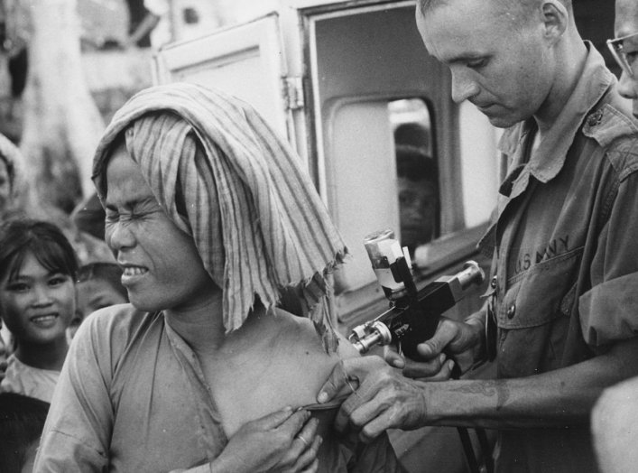 A U.S. Navy hospital corpsman, member of a USAID military health team, inoculates a flood refugee against cholera at the refugee center on Nui Sam mountain, Chau Doc province., 1966. U.S. Information Agency via National Archives and Records Administration