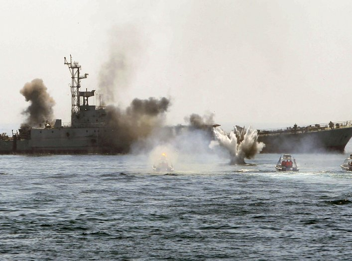 An Iranian warship and speed boats take part in a naval war game in the Persian Gulf and the Strait of Hormuz, southern Iran April 22, 2010. Iran's Revolutionary Guards successfully deployed a new speed boat capable of destroying enemy ships as war games.