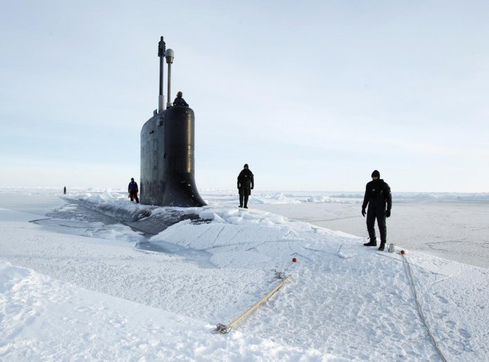 U.S. Navy safety swimmers stand on the deck of the Virginia class submarine USS New Hampshire after it surfaced through thin ice during exercises underneath ice in the Arctic Ocean north of Prudhoe Bay, Alaska March 19, 2011. REUTERS/Lucas Jackson