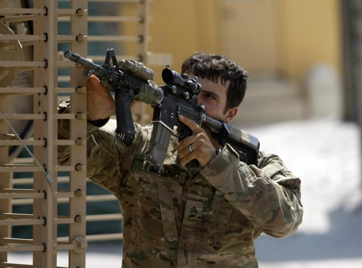 U.S. army soldier from 2-35 Infantry Battalion aims his weapon as he looks for a source of gun fire and rocket propelled grenades fired by the Taliban at a forward firebase fortress in Kunar province, Afghanistan, July 11, 2011. REUTERS/Baz Ratne
