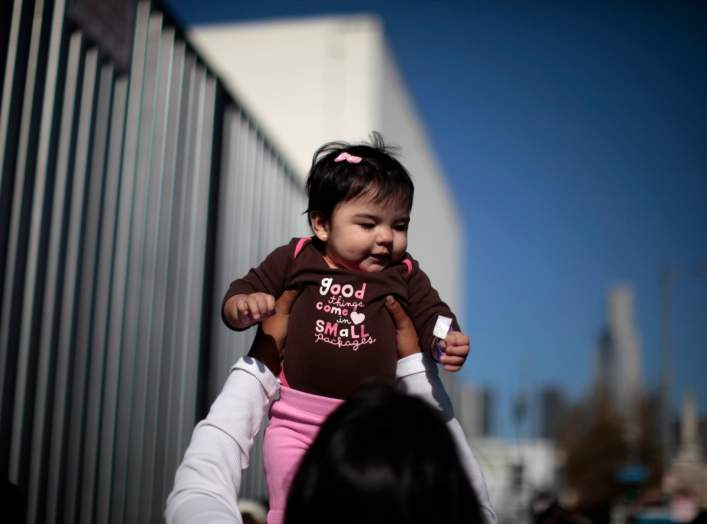 "A woman plays with a baby as they wait to go into a ""Back-to-School"" giveaway at the Fred Jordan Mission in Los Angeles, California October 6, 2011."