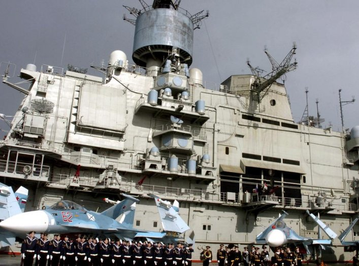 Naval personnel stand in front of the Russian aircraft carrier Kuznetsov in the Syrian city of Tartous on the Mediterranean sea January 8, 2012, in this handout photograph released by Syria's national news agency SANA. QUALITY FROM SOURCE. REUTERS/SANA/Ha