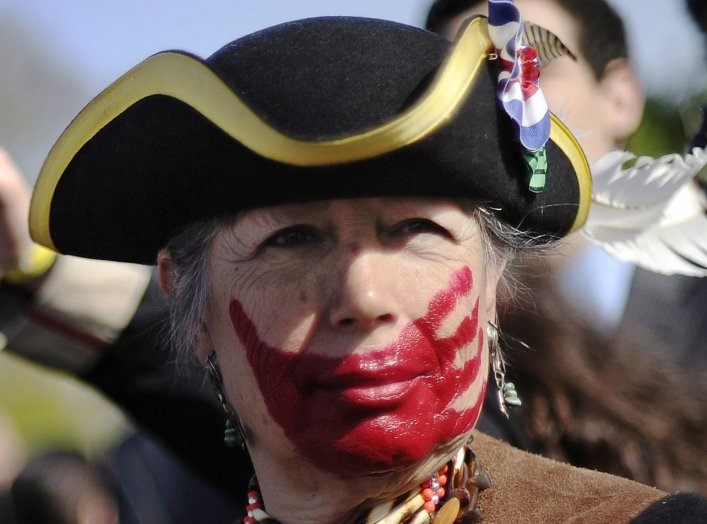 Tea party supporter Susan Clark of California, dressed in colonial garb and face paint, protests against the Obama healthcare legislation as the law's supporters and detractors rally on the sidewalk in front of the Supreme Court, during the third and fina