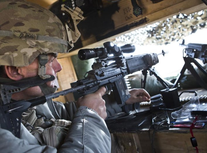 A soldier from 1st Platoon, Alpha Company, 1st Battalion, 36th Infantry Regiment, looks down the scope of his M14 rifle after an improvised explosive device (IED) detonated approximately 800 meters away from strong point DeMaiwand, Maywand District, Kanda