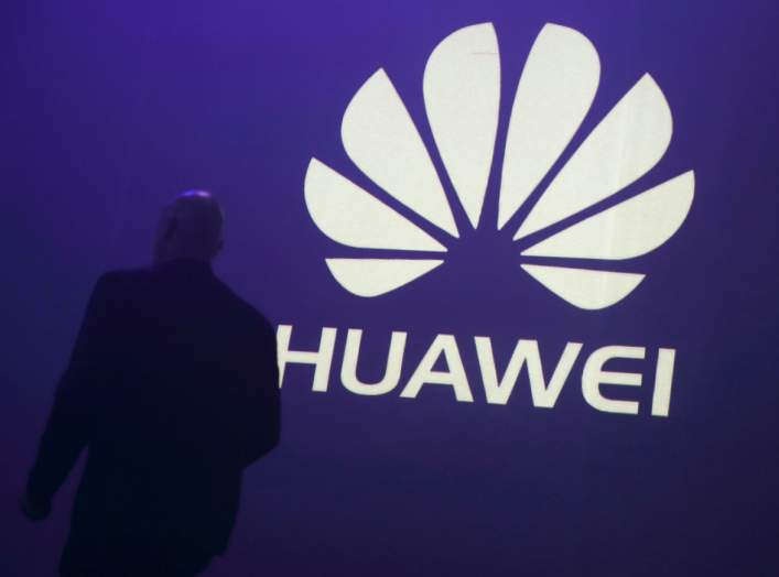 A man walks past a logo during the presentation the Huawei's new smartphone, the Ascend P7, launched by China's Huawei Technologies in Paris, May 7, 2014.