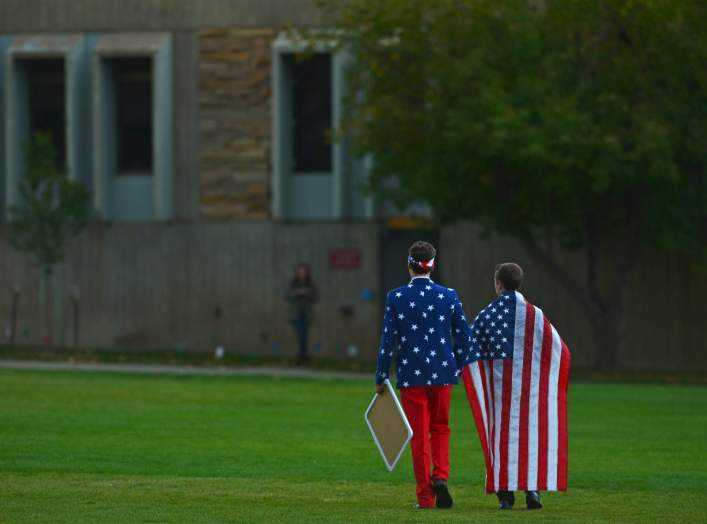"People wear the American flag as students and protesters gather at the ""Free Speech Zone"" located at the University of Colorado's Business Field, while candidates gather across the street for a forum held by CNBC, before the U.S. Republican presidential c"