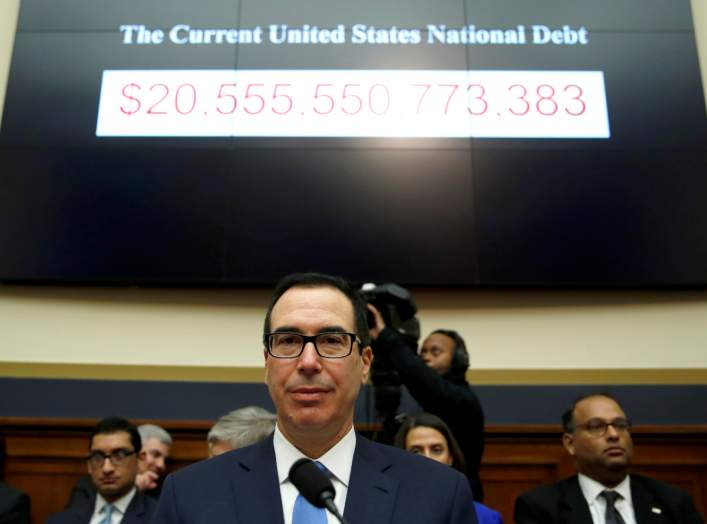 "Treasury Secretary Steven Mnuchin sits under a display of the U.S. national debt as he testifies to the House Financial Services Committee on ""The Annual Report of the Financial Stability Oversight Council"" on Capitol Hill in Washington, U.S., February 6,"