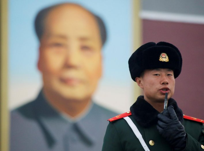 A paramilitary police officer stands guard in Tiananmen Square after a flag raising ceremony in front of a portrait of the late Chinese Chairman Mao Zedong ahead of the upcoming plenary session of National People's Congress (NPC), China's parliamentary bo