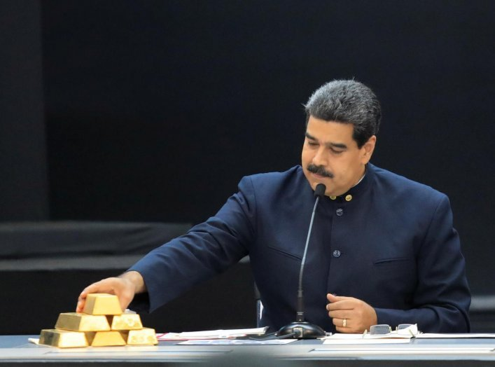 Venezuela's President Nicolas Maduro touches a gold bar as he speaks during a meeting with the ministers responsible for the economic sector at Miraflores Palace in Caracas, Venezuela March 22, 2018. REUTERS/Marco Bello