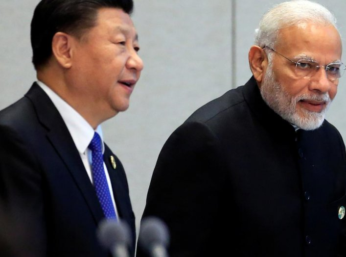 China's President Xi Jinping and India's Prime Minister Narendra Modi arrive for a signing ceremony during Shanghai Cooperation Organization (SCO) summit in Qingdao, Shandong Province, China June 10, 2018. REUTERS/Aly Song