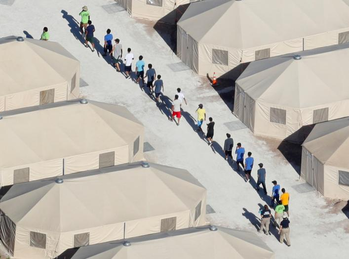 "Immigrant children now housed in a tent encampment under the new ""zero tolerance"" policy by the Trump administration are shown walking in single file at the facility near the Mexican border in Tornillo, Texas, U.S. June 19, 2018. REUTERS/Mike Blake"