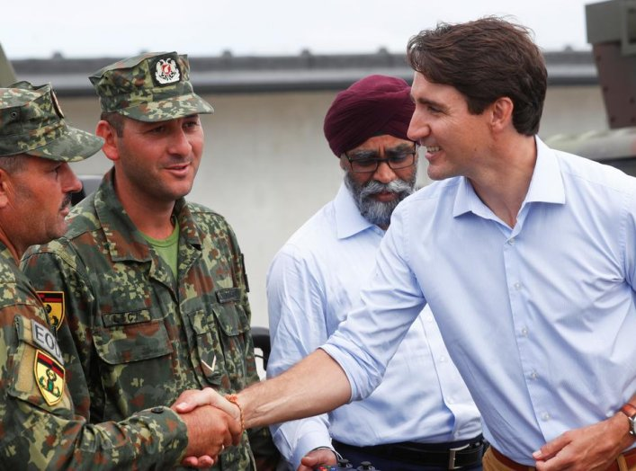 Canada's Prime Minister Justin Trudeau, accompanied by Canada's Defence Minister Harjit Sajjan, shakes hands with Albanian soldiers as he visits NATO eFP Canadian-led battlegroup troops in Adazi military base, Latvia July 10, 2018. REUTERS/Ints Kalnins