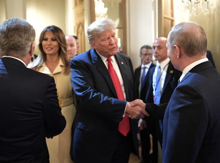 Russia's President Vladimir Putin (R) shakes hands with U.S. President Donald Trump as First lady Melania Trump stands nearby during a meeting in Helsinki, Finland July 16, 2018. Sputnik/Alexei Nikolsky/Kremlin via REUTERS