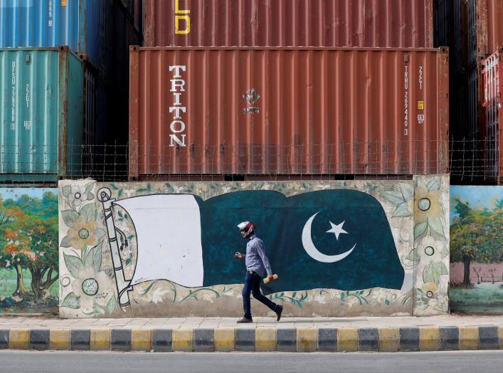 A man walks past a wall of a shipping container's yard painted with a national flag ahead of Pakistan's Independence Day, in Karachi, Pakistan August 6, 2018. REUTERS/Akhtar Soomro