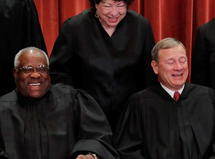 U.S. Supreme Court Associate Justice Sonia Sotomayor makes Associate Justice Clarence Thomas and Chief Justice John Roberts laugh as they pose together for their group portrait at the Supreme Court in Washington, U.S., November 30, 2018. REUTERS/Jim Young