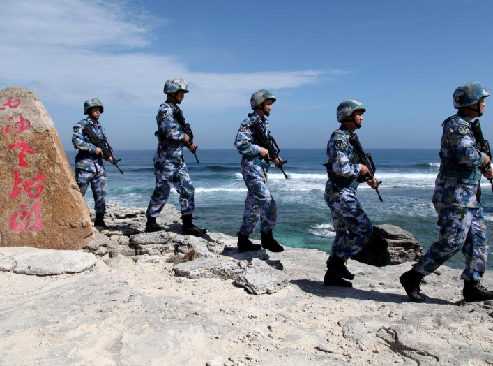 "Soldiers of China's People's Liberation Army (PLA) Navy patrol at Woody Island, in the Paracel Archipelago, which is known in China as the Xisha Islands, January 29, 2016. The words on the rock read, ""Xisha Old Dragon"". Old Dragon is the local name of a p"
