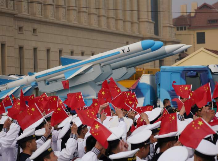 Chinese People's Liberation Army (PLA) Navy soldiers wave Chinese flags next to a model of a military vehicle carrying anti-ship missiles, during an event marking the 70th anniversary of the founding of Chinese People's Liberation Army Navy on April 23