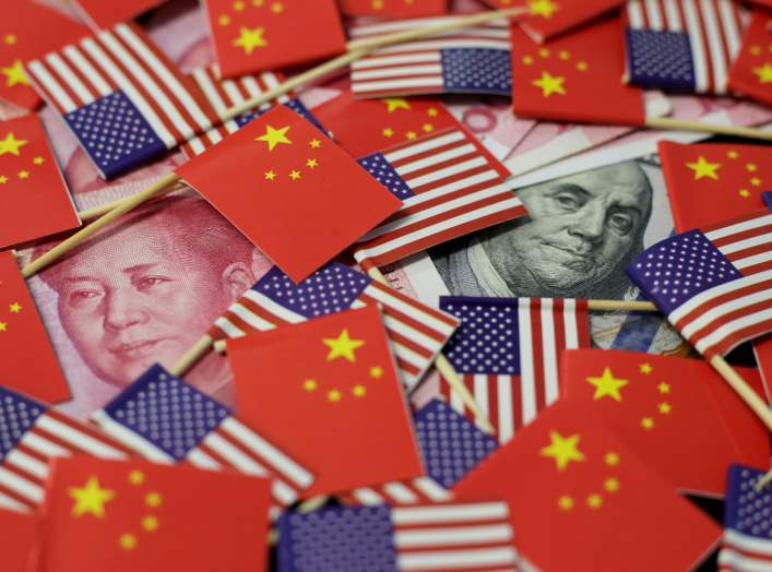 A U.S. dollar banknote featuring American founding father Benjamin Franklin and a China's yuan banknote featuring late Chinese chairman Mao Zedong are seen among U.S. and Chinese flags in this illustration picture taken May 20, 2019. REUTERS/Jason Lee