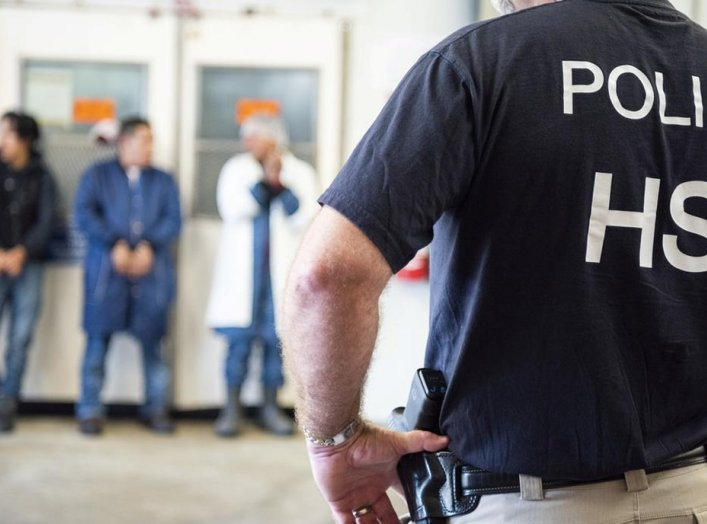 Image: Homeland Security Investigations (HSI) officers from Immigration and Customs Enforcement (ICE) look on after executing search warrants and making some arrests at an agricultural processing facility in Canton, Mississippi, U.S. in this August 7, 201