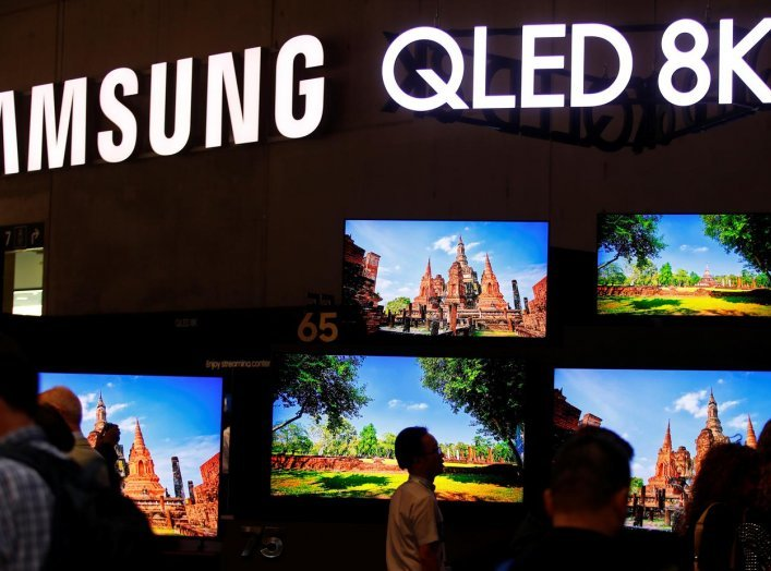 People stand in front of the QLED 8K screens at the hall of Samsung at the IFA consumer tech fair in Berlin, Germany, September 6, 2019. REUTERS/Hannibal Hanschke