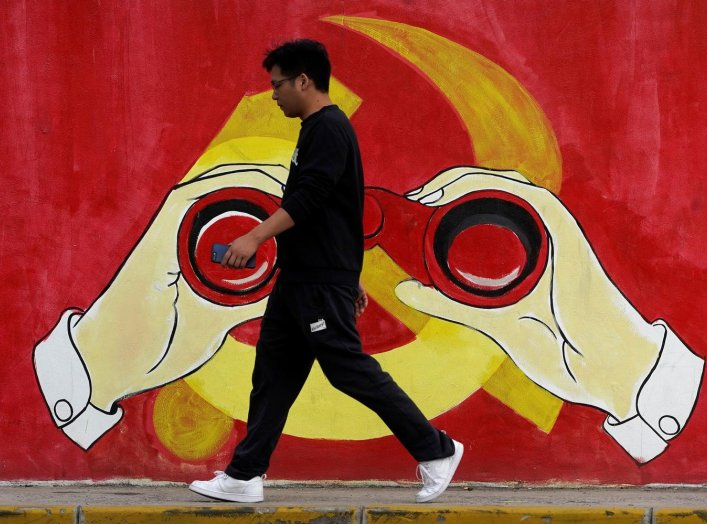 A man walks next to a mural showing an image of the Chinese Communist Party's emblem along a street in Shanghai, China September 25, 2019. REUTERS/Aly Song