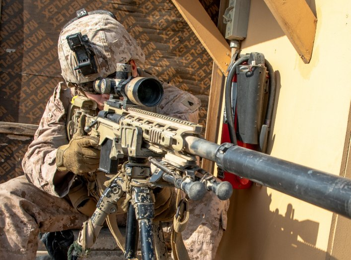 A U.S. Marine with 2nd Battalion, 7th Marines, assigned to the Special Purpose Marine Air-Ground Task Force-Crisis Response-Central Command (SPMAGTF-CR-CC) 19.2, looks through the scope of a M110 Semi-Automatic Sniper System (SASS) at the U.S. embassy com