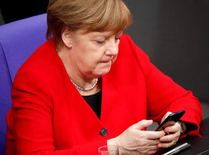 FILE PHOTO: German Chancellor Angela Merkel checks her phone at the lower house of parliament (Bundestag), ahead of a Brussels summit for Brexit delay discussions, in Berlin, Germany March 21, 2019. REUTERS/Hannibal Hanschke/File Photo