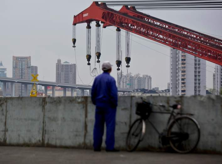 FILE PHOTO: FILE PICTURE: A worker stands by a dock next to the Huangpu river in Shanghai, Nov. 25, 2014. REUTERS/Aly Song/File Photo