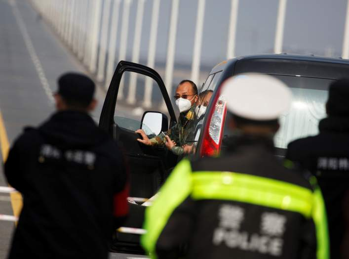 A man arrives from Hubei province at a checkpoint at the Jiujiang Yangtze River Bridge as the country is hit by an outbreak of the novel coronavirus, in Jiujiang, Jiangxi province, China, February 4, 2020. REUTERS/Thomas Peter