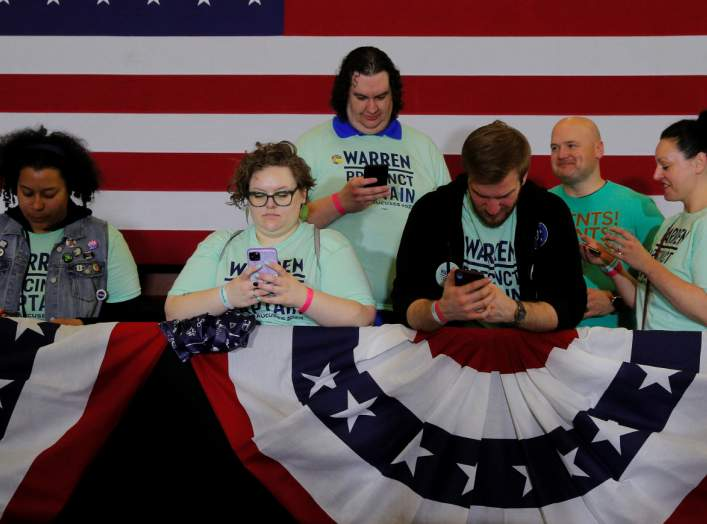 Supporters of Democratic 2020 U.S. presidential candidate and U.S. Senator Elizabeth Warren (D-MA) look at their mobile phones before she speaks at her Iowa Caucus rally in Des Moines, Iowa, U.S., February 3, 2020. Picture taken February 3, 2020. REUTERS/