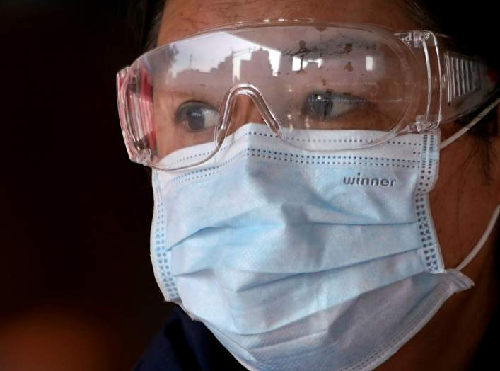 FILE PHOTO: A passenger wearing a mask walk outside the Shanghai railway station in Shanghai, China, as the country is hit by an outbreak of a new coronavirus, February 4, 2020. REUTERS/Aly Song/File Photo