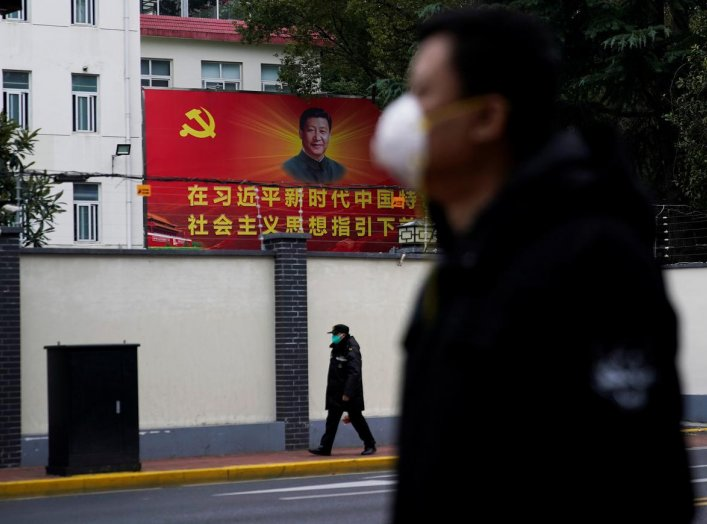 People wearing masks walk past a portrait of Chinese President Xi Jinping on a street as the country is hit by an outbreak of the novel coronavirus in Shanghai, China February 10, 2020. REUTERS/Aly Song