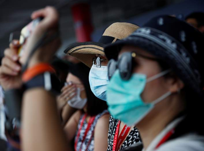 Spectators wearing masks in precaution of the coronavirus outbreak watch an aerial display at the Singapore Airshow in Singapore February 11, 2020. REUTERS/Edgar Su