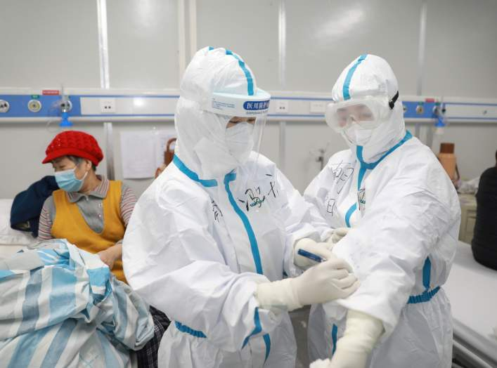 A medical worker writes down a patient's dietary information on a colleague's protective suit inside Leishenshan hospital, a makeshift hospital to treat patients with the novel coronavirus, in Wuhan, Hubei province, China February 16, 2020. Picture taken
