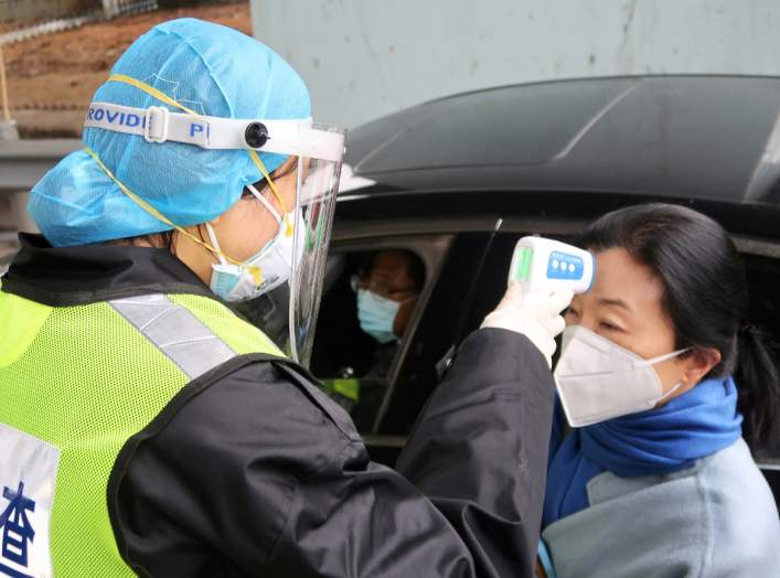 A security officer in a protective mask checks the temperature of a passenger following the outbreak of a new coronavirus, at an expressway toll station on the eve of the Chinese Lunar New Year celebrations, in Xianning, a city bordering Wuhan to the nort